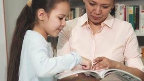 Мать и дочь выбирая книги на библиотеке или bookstore стоковое фото