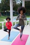 Мать и дочь выполняя йогу в крылечке Стоковые Изображения
