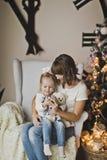 Мать и дочь в белом стуле перед огромными часами Стоковое Изображение RF