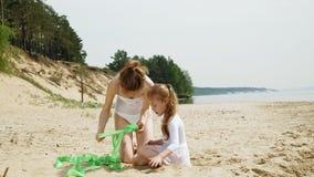 Мать и дочь в белых купальных костюмах танцуя с гимнастической лентой на песчаном пляже Лето, рассвет сток-видео