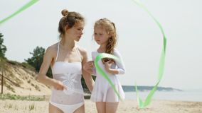 Мать и дочь в белых купальных костюмах танцуя с гимнастической лентой на песчаном пляже Лето, рассвет акции видеоматериалы