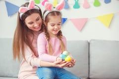 Мать и дочь в зайчика ушей торжестве пасхи совместно дома держа смеяться над яичек Стоковые Фото