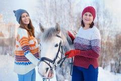 Мать и дочь в зиме с красивой белой лошадью стоковая фотография rf