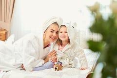 Мать и дочь в купальных халатах и полотенцах на кровати в ro Стоковые Изображения