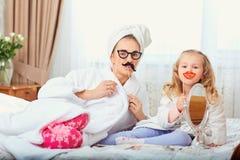 Мать и дочь в купальных халатах и полотенцах на кровати в ro Стоковые Фото