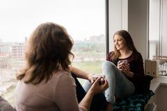 Мать и дочь говоря пока имеющ чай дома Стоковое фото RF