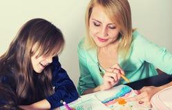Мать и дочь делая домашнюю работу стоковое фото