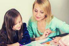 Мать и дочь делая домашнюю работу стоковые фото