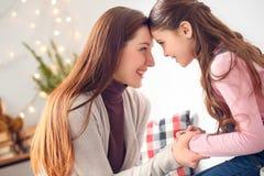 Мать и дочь дома сидя смотрящ усмехаться лбов одина другого совместно счастливый стоковая фотография