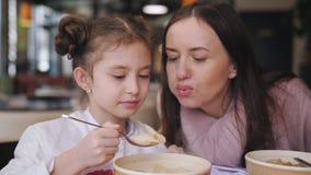 Мать и дочь есть горячую еду на ресторане Мама пробует охладить еду к его маленькой дочери акции видеоматериалы