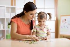 Мать и дочь играя дома Они собирая мозаика Стоковая Фотография