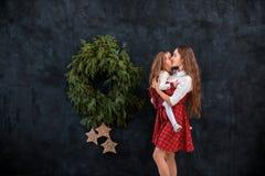 Мать и дочь играя около венка рождества стоковое фото rf