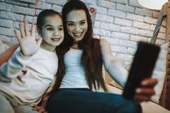 Мать и дочь имеют видео- звонок по телефону стоковое фото
