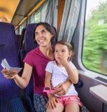 Мать и дочь имея ее билет быть проверенным проводником поезда стоковое фото rf