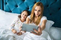 Мать и дочь лежа на кровати и принимая автопортрет с smartphone Женщина принимая selfie с маленькой девочкой в спальне Стоковые Изображения