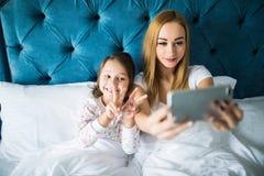 Мать и дочь лежа на кровати и принимая автопортрет с smartphone Женщина принимая selfie с маленькой девочкой в спальне Стоковое Фото