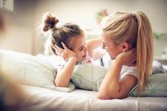 Мать и дочь лежа на кровати смотря etch другое Стоковые Фото