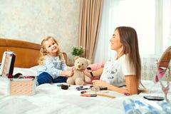 Мать и дочь макетируют, сыграть на кровати окном Стоковые Изображения