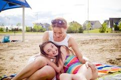 Мать и дочь на говорить пляжа стоковые фото