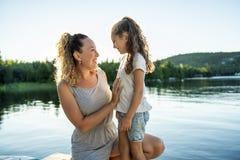Мать и дочь на летний день пристани теплый имея полезного время работы стоковая фотография rf