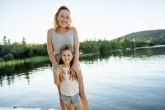 Мать и дочь на летний день пристани теплый имея полезного время работы стоковое изображение