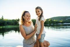 Мать и дочь на летний день пристани теплый имея полезного время работы стоковые фотографии rf