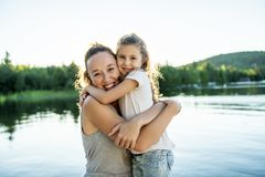 Мать и дочь на летний день пристани теплый имея полезного время работы стоковые фото