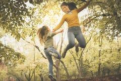 Мать и дочь на лужке Toget матери и дочери скача стоковое фото
