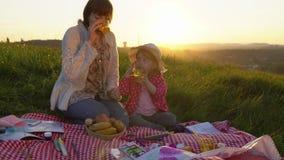 Мать и дочь на пикнике на холме в лете на заходе солнца акции видеоматериалы