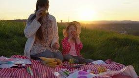 Мать и дочь на пикнике на холме в лете на заходе солнца сток-видео
