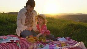 Мать и дочь на пикнике на холме в лете на заходе солнца видеоматериал