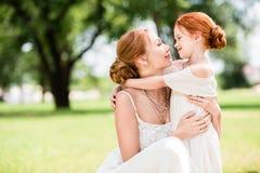 Мать и дочь обнимая на парке Стоковые Изображения