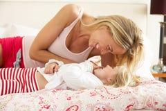Мать и дочь ослабляя совместно в кровати Стоковое Изображение RF