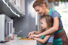 Мать и дочь подготавливая салат в кухне Стоковое Изображение