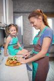 Мать и дочь подготавливая салат в кухне Стоковое фото RF