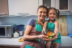 Мать и дочь подготавливая салат в кухне Стоковое Изображение RF