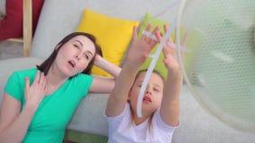 Мать и дочь портрета рядом с вентилятором страдают от жаркой погоды акции видеоматериалы
