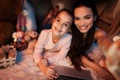 Мать и дочь принимая selfie в доме подушки поздно на ночу дома стоковая фотография