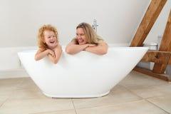 Мать и дочь рассматривая край freestanding ванны стоковые изображения rf