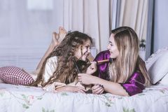 Мать и дочь самостоятельно дома красивая, модная и потеха стоковая фотография
