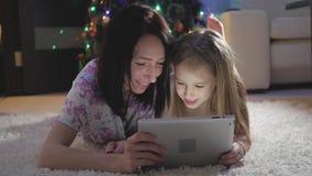 Мать и дочь семьи выбирая подарки на цифровом планшете пока ложь на поле время конца рождества предпосылки красное вверх акции видеоматериалы