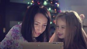 Мать и дочь семьи выбирая подарки на цифровом планшете пока ложь на поле время конца рождества предпосылки красное вверх видеоматериал