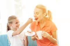 Мать и дочь сидят на кресле в светлой комнате Они едят торт стоковые изображения rf