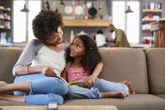 Мать и дочь сидят на софе в книге чтения салона совместно стоковая фотография rf
