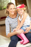 Мать и дочь сидя вне дома Стоковая Фотография RF