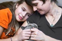 Мать и дочь сидя совместно и штрихуя чистоплеменного кота стоковое фото