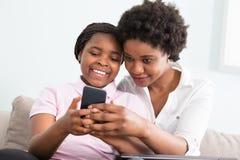 Мать и дочь смотря умный телефон Стоковое Фото