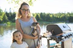 Мать и дочь и собака на летний день пристани теплый имея полезного время работы стоковая фотография rf