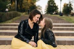 Мать и дочь совместно смотрят один другого и получают женатыми они сидят на лестницах в парке мать s дня стоковая фотография