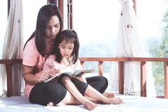 Мать и дочь счастливой семьи азиатская прочитали книгу совместно Стоковые Изображения RF